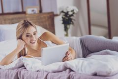 Pretty young woman lying on bed and watching video royalty free stock images
