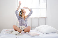 Amusing content girl listening music and dancing on bed Royalty Free Stock Photo