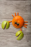 Amusing crab made of fruits. On desk royalty free stock photography