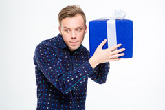 Amusing curious man trying to listen something inside present box. Amusing curious blond man in plaid shirt trying to listen something inside present box over royalty free stock photos