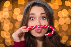 Amusing cute curly girl making funny face using candy cane Royalty Free Stock Image