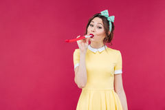 Amusing cute young woman standing and blowing in party whistle Royalty Free Stock Photos