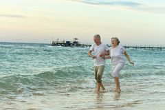 Amusing elderly couple on a beach. Amusing elderly couple went to the beach to have a walk by sea Stock Photos