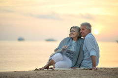 Amusing elderly couple. Went to the beach to enjoy the sea breeze Stock Photos