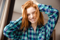 Amusing funny girl in checkered shirt with tousled red hair. Amusing cheerful funny girl in blue checkered shirt with tousled red hair at home Royalty Free Stock Image