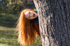 Amusing funny girl  looking out from the tree in park Stock Image