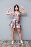 Amusing funny girl showing her biceps. Amusing funny pretty cheerful girl in floral top and skirt and sneackers showing her biceps stock photos