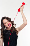 Amusing funny retro styled woman imitating choking with telephone cable Royalty Free Stock Images