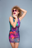 Amusing funny young woman in sunglasses posing on gray backgroung Stock Photo