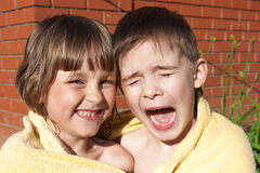 An amusing girl and boy are wrapped in a towel Royalty Free Stock Images