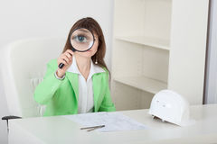 Amusing girl looks at us through big magnifier Stock Image