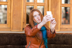 Amusing girl making funny faces and taking photos of herself. Amusing cute redhead girl in leather jacket and scarf making funny faces and taking photos of stock photography
