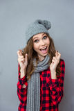 Amusing girl in scarf and hat smiling with crossed fingers Royalty Free Stock Photography