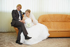 Amusing groom and bride sitting on armchair Stock Images