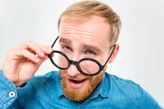 Amusing happy man with beard looking over his round glasses Stock Photos