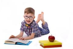 Amusing joyful kid reads books lying on a floor Stock Image