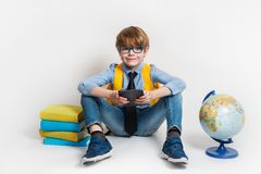 Boy reading ebook. Back to school and happy time. Amusing joyful kid reads eBook sitting on a floor. Education Royalty Free Stock Photos