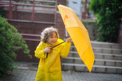 The amusing little boy in a yellow raincoat and with umbrella stand at rain. Royalty Free Stock Image