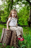 Amusing little girl sits on a hemp Stock Photos