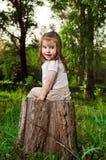 Amusing little girl sits on a hemp Stock Photos