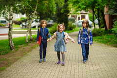 Amusing little school students go to school having joined hands. Royalty Free Stock Image