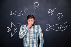 Amusing man closed nose and standing over chalkboard with fishes Royalty Free Stock Image