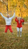 Amusing old couple. Amusing happy smiling old couple on yellow autumn park background Royalty Free Stock Images