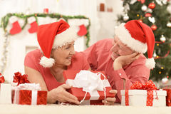 Amusing old couple at Christmas. Amusing old couple wearing Christmas holiday caps royalty free stock photos