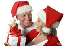 Amusing old couple with gift. Celebrating New Year royalty free stock photography