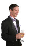 Amusing Party Story. A handsome man in a tuxedo, with a glass of champagne, laughing at an amusing story stock photos