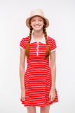 Amusing positive girl with two braids in boonie hat. Portrait of amusing positive redhead girl with two braids in boonie hat and casual dress posing on white Stock Image