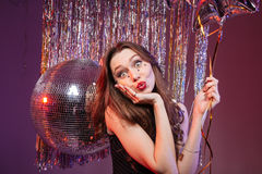 Amusing pretty woman holding balloon and sending a kiss. Amusing pretty young woman holding balloon and sending a kiss over purple background royalty free stock images