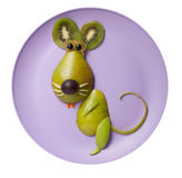 Amusing rat made of fruits. On purple plate Stock Image