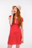 Amusing redhead girl in boonie hat eating apple Royalty Free Stock Photos