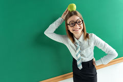 Amusing schoolgirl with an apple on her head. Royalty Free Stock Photography