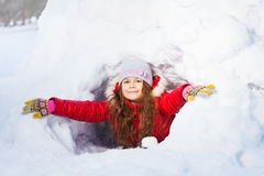 Amusing smiling girl in the winter at a snow cave Royalty Free Stock Photography
