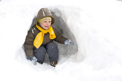 Amusing smiling kid in the winter. In a snow cave Stock Images
