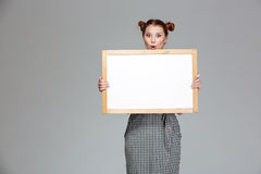 Amusing surprised young woman holding blank whiteboard Stock Photography