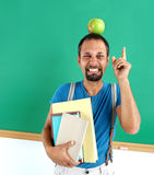 Amusing teacher literature with an apple on her head. Royalty Free Stock Images