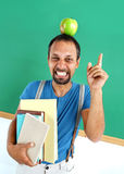 Amusing teacher literature with an apple on her head. Royalty Free Stock Photos