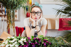 Amusing woman florist making funny face standing in flower shop Royalty Free Stock Images