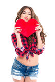 Amusing woman holding red heart and making funny duck face Royalty Free Stock Images