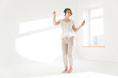 Amusing woman listening to music from cell phone and dancing Royalty Free Stock Image