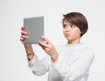 Amusing woman making funny face and taking selfie with tablet. Amusing pretty young woman with short haircut making funny face and taking selfie with tablet over Royalty Free Stock Photography