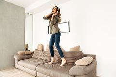 Amusing woman 20s in casual clothing partying at home and dancin. G on couch while listening to music via wireless earphones Royalty Free Stock Photo