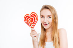 Amusing woman showing tongue and holding heart shaper lollipop. Amusing attractive young woman showing tongue and holding heart shaper lollipop over white Stock Photos