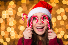 Amusing young female making funny face using christmas lollypops Royalty Free Stock Images