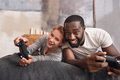 Amusing young international couple playing games at home. Enjoyable atmosphere around us . Joyful easygoing friendly international couple lying in the bedroom Royalty Free Stock Photography