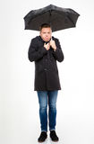 Amusing young man standing and feeling cold under umbrella Stock Photos