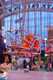 Amusment Park Ride. A seat on an amusement park ride sits vacant, suspended by chains, waiting for a rider Stock Images